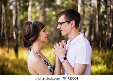 Beautiful girl with dark hair and in summer dress hugging a man in a white shirt. Loving couple in the forest on a sunny day. To love each other