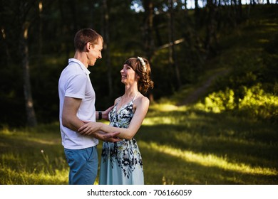 Beautiful girl with dark hair in summer dress hugging a man in a white shirt on a green background. Loving couple in the forest on a sunny day. To love each other