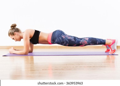 Beautiful girl with dark hair wearing pink snickers, dark leggings and black short top doing plank at gym, fitness, white wall and wooden floor.