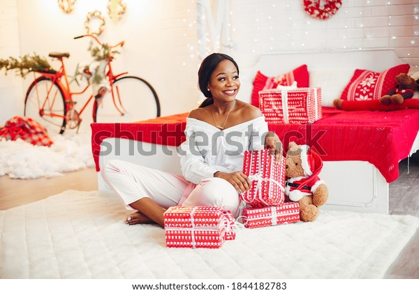 Beautiful girl in a decorated room. Woman near Christmas tree. Black lady in a white blouse