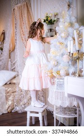 beautiful girl decorates a Christmas tree standing on a chair . New Year