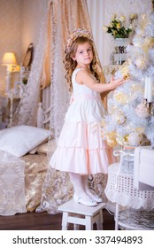beautiful girl decorates a Christmas tree standing on a chair against a background of the bedroom , light the lamp in the corner . New Year 's Eve