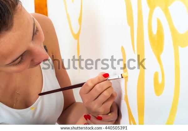 Beautiful girl decorating wall