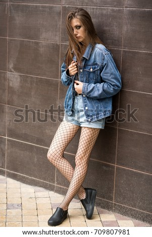 e14d6049a10 Beautiful girl in denim shorts and jeans jacket in the street. Rock style.  Fashionable
