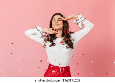 Beautiful girl with dimpled cheeks is smiling. Woman in stylish outfit smacks on pink background