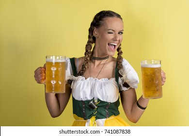 Beautiful girl in a dirndl winking and holding mugs filled with beer on yellow background, Oktoberfest portrait