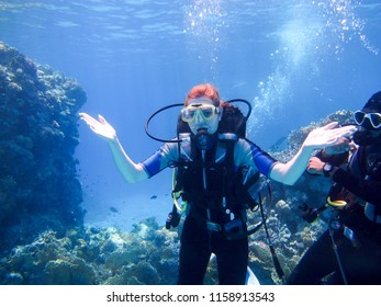 A beautiful girl diver shows hands gesture signal all well with a partner instructor for safety floats under the water in the red sea with coral reefs Egypt, Sharm el-Sheikh, 05/15/2018.