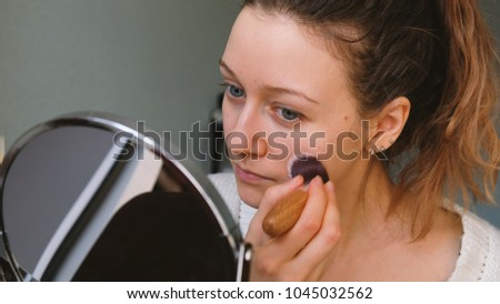 Beautiful girl does make-up in front of a mirror, puts a powder whale, 4k