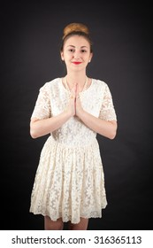 Beautiful girl doing different expressions in different sets of clothes: prayer
