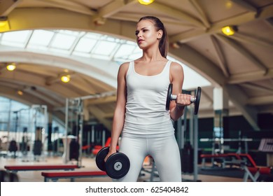 Beautiful girl doing exercises with dumbbells in the gym dressed blank white tank-top and tights.