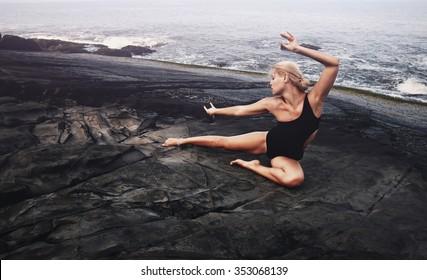 Beautiful girl doing exercises on the coast