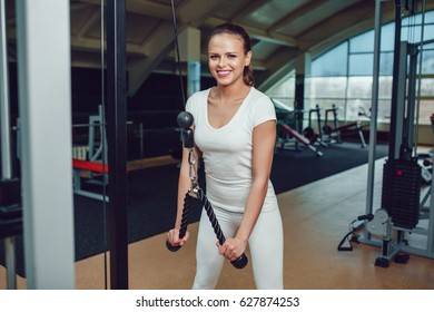 Beautiful girl doing exercises on the simulator in the gym dressed blank white t-shirt and tights. Mock up.