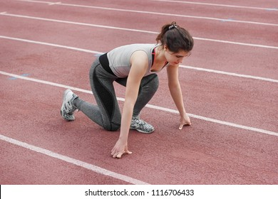 Beautiful girl doing exercises at the stadium for athletics. The girl has a beautiful, slender body. She trains in sports clothes.