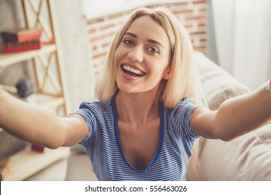 Beautiful girl is doing selfie and smiling while sitting on couch at home