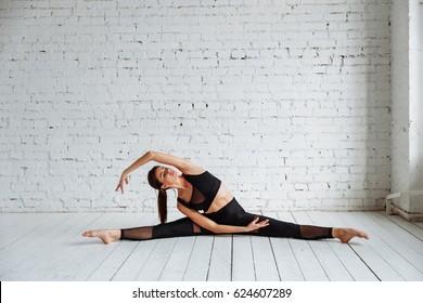 красивая девушка делает упражнения на растяжение в балетной школе. черный эластичный костюм для йоги