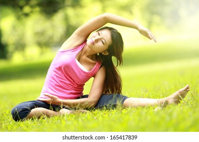 beautiful girl doing workout on grass in the morning