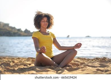 Beautiful girl doing yoga at the beach