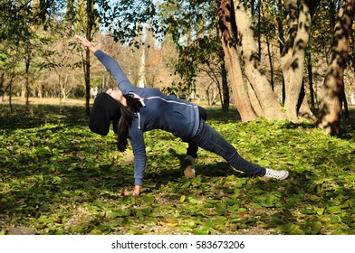 Beautiful girl doing yoga at the park at a sunny day. Camatkarasana, Wild thing pose.