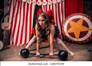 Beautiful girl with doll face with red bow on her head tries to lift a heavy dumbbell