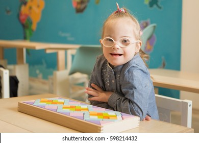 Beautiful girl with down syndrome engaged in class