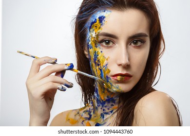 beautiful girl with drawn multicolor paint makeup looking at camera