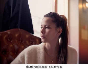 Beautiful girl dreaming about something while sitting in a cafe and looking at window. Young charming woman thinking about new ideas, drink a coffee, sitting on a leather sofa in a modern city bar.