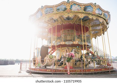 Beautiful girl in a dress with a bouquet of pink peonies in the hands near a vintage carousel