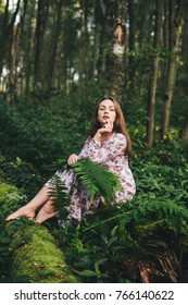 Beautiful girl in a dress in the forest among the fern. toning
