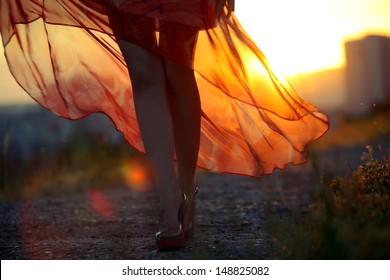 beautiful girl in dress on sunset