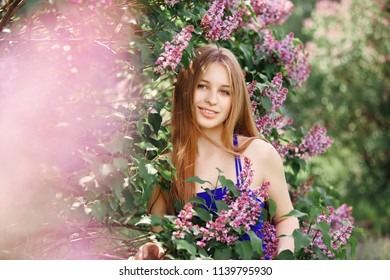 Beautiful Girl in a dress posing near a Bush of lilacs on a summer day, purple flowers. Spring portrait of a child in the Park. Sverdlovsk, June 20, 2018
