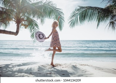 Beautiful girl in a dress and sunglasses posing on the beach, beauty portrait, fashion woman, red lipstick, tanned skin, portrait, sea, sunny island, Bali, hat, cap, jump, palms