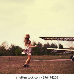 Beautiful girl in a dress in the wind in a field of flowers around the aircraft