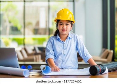 Beautiful girl dressed as an architect and working on a blueprint and near the girl is Laptop, Book, Construction planning drawings.