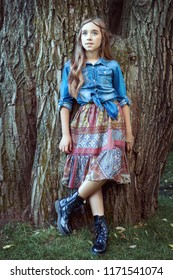 Beautiful girl dressed in boho style standing at tree.
