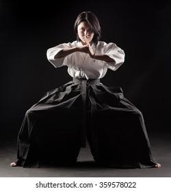 beautiful girl dressed in hakama practicing Aikido in a dark gym