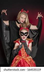 beautiful girl dressed as Halloween vampire attacking a child vampire   isolated on dark red  background