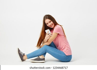 Beautiful girl dressed in a pink t-shirt, jeans and sneakers sits on the floor and uses mobile phone on a white background in the studio