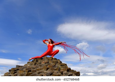 A beautiful girl dressed in red poses on the top of a stone wall with blue sky behind her. Red ribbons which are attached to her costume are dramatically flying in a wind.