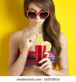 Beautiful girl drinking a cocktail against yellow background.