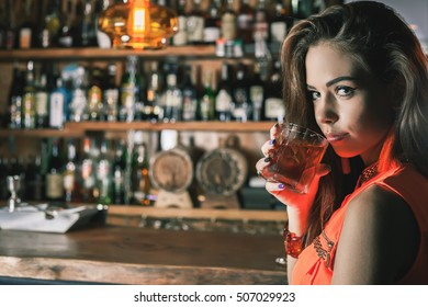 Beautiful girl is drinking a cocktail with ice vapor in the bar. Nightclub. Young woman looking at camera
