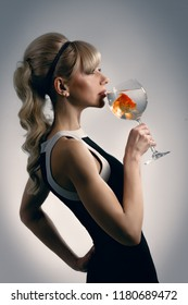 Beautiful girl drinking glass of water with golden fish and making wish
