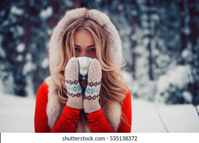 beautiful girl is drinking a hot drink from a cup in the winter in nature, tea, coffee