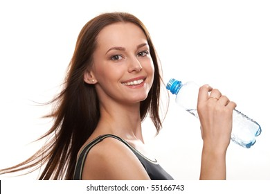 Beautiful girl drinking water from blue bottle on blue background