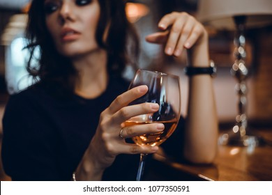 Beautiful girl in drinks Aperol Spritz wine from a glass in a restaurant, a cafe, has a good weekend, a stylish fashionable woman, a brunette young, emotional, outdoor close up hipster portrait
