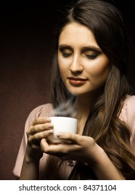 beautiful girl drinks coffee in the kitchen