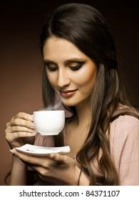 beautiful girl drinks coffee in the kitchen