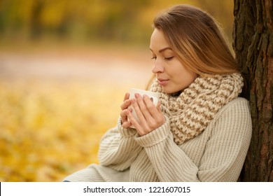Beautiful girl drinks warm tea, hot shikolad, coffee in a warm autumn park. Concept of autumn warmth, atmosphere and comfort. With space for an inscription