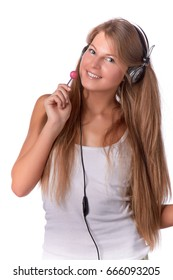 The beautiful girl with earphones and lollipop listens to music on a white background.