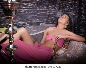beautiful girl in eastern dress smokes a hookah