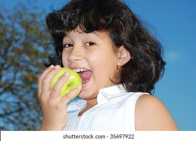 Beautiful girl eating an apple outdoor